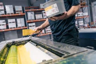 Mann trägt Farbe für Bogendruck in Druckmaschine auf Von Stern'sche Druckerei