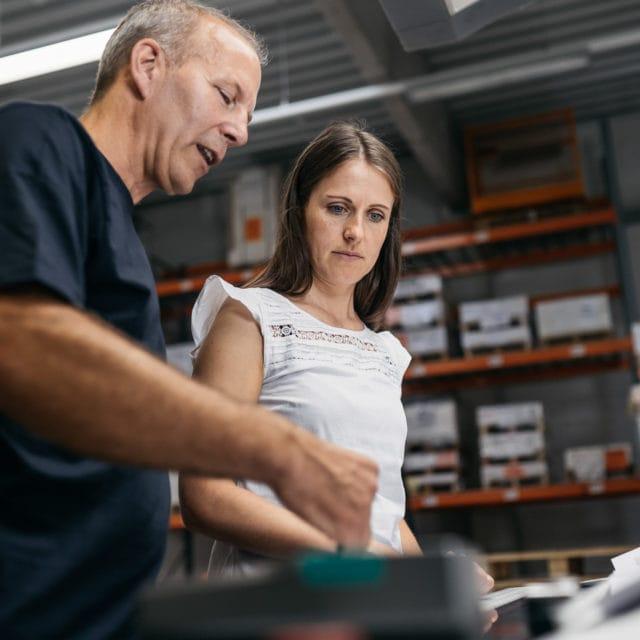 Mitarbeiter berät Kundin zu Offsetdruck von Stern'sche Druckerei Lüneburg