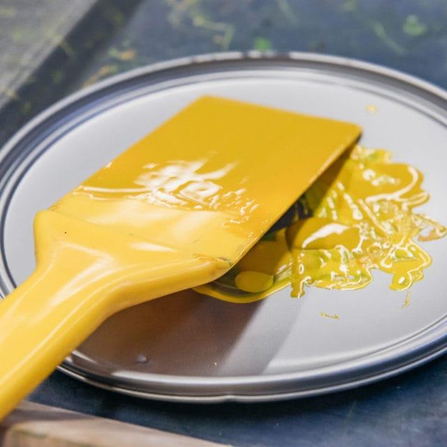 Pinsel mit gelber Farbe auf einem Farbdeckel von ökologischer Farbe für Bogendruck bei der Sternsche Druckerei