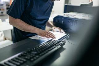 Mann überprüft hochwertigen Digitaldruck in Lüneburg bei von Stern'sche Druckerei