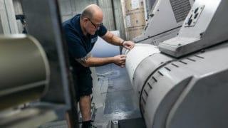 Mitarbeiter im Zeitungsdruck bei der von Stern'sche Druckerei in Lüneburg bereitet Papierrolle vor