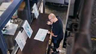 Mann kontrolliert Druckplatten für Zeitungsdruck Druckerei von Stern'sche