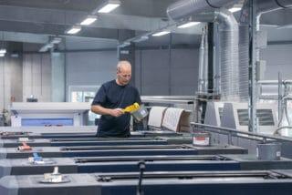 Mitarbeiter streicht beim Bogen-Offsetdruck den Drucker mit Farbe ein in der Druckerei von Stern'sche