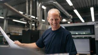 Mitarbeiter Mann lachend Testdruck Magazin Bogendruck Druckerei von Stern'sche