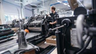 Mann an der Druckplatte. Druckerzeugnisse in großen Mengen konfektionieren, Heften, Falzen und ausliefern. Alles bei von Stern'sche Druckerei Lüneburg
