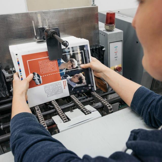 Weiterverarbeitung Mitarbeiterin bei der von Stern'sche Druckerei Lüneburg verarbeitet Broschüren individuell weiter