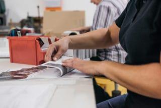 Individuelle Druckerzeugnisse werden händisch von Mitarbeitern geprüft und gefaltet Von Stern'sche Druckerei