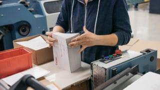 Printprodukte weiterverarbeiten: Mitarbeiter zählt und faltet Prospekte